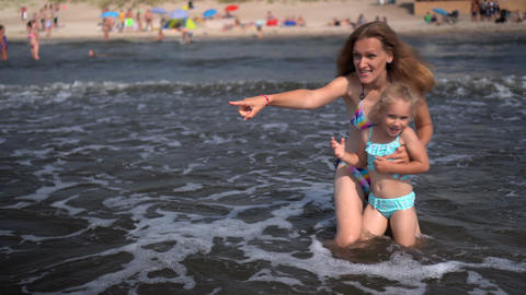 Playful woman and daughter facing sea waves. Emotional girls get water splashed Live Action