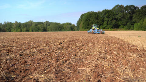 Blurred blue tractor discing stubble field soil with special equipment Live Action