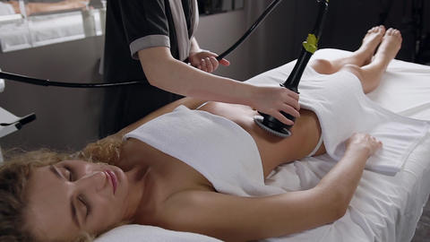 Gorgeous blond woman with curly hair enjoying stomach massage using for that Live Action