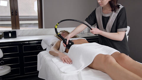 Slow motion of attractive female beautician which doing rf-lifting massage on Live Action
