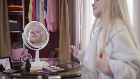 Pretty Caucasian little girl admiring her reflection in mirror. Portrait of cute Live Action