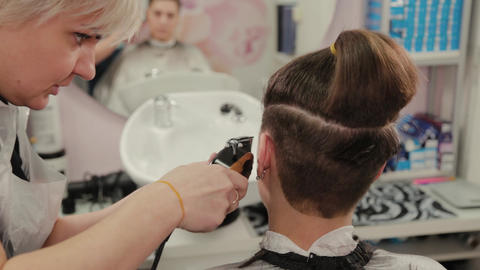 Professional hairdresser woman cutting hair to client with hair clipper Live Action