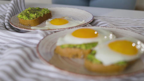 Woman puts fried eggs on a plate with avocado toast. Healthy vegan breakfast Live Action