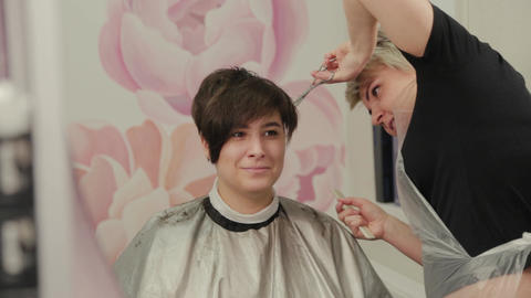 Professional hairdresser woman haircuts a girl with a hairdresser Live Action