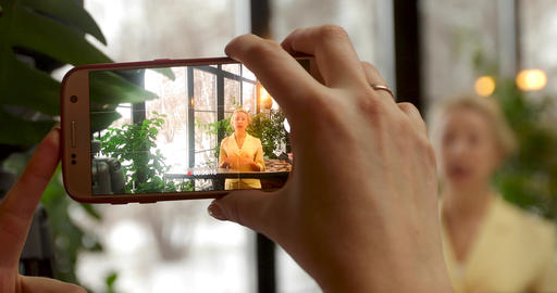 Anonymous woman taking photo of lady on smartphone Live Action