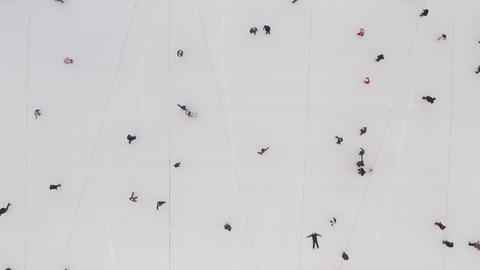 Top view of people sliding on the ice of an ice rink in the fresh air in the Live Action