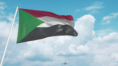 Commercial airplane landing behind the Sudanian flag. Tourism in Sudan Live Action