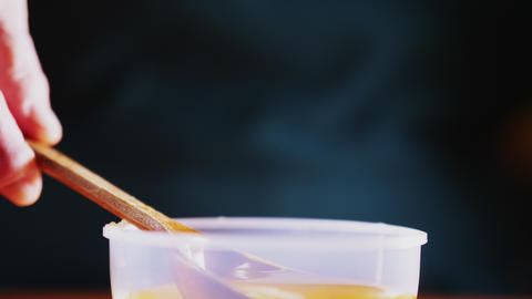 person pours tasty honey from spoon on dark background Live Action