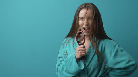 Overjoyed lady dancing in bathrobe and singing into brush Live Action
