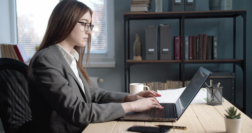 Side view of serious lady working on laptop at modern office Live Action
