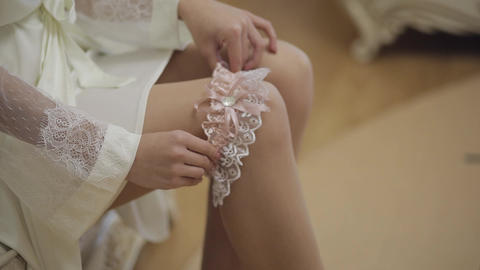 Legs of bride in night gown and veil. Sitting on a sofa and puts garter on a leg Live Action
