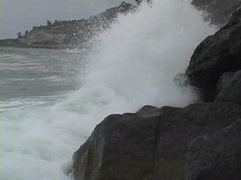 Waves splash against rocks as they hit the shore Footage