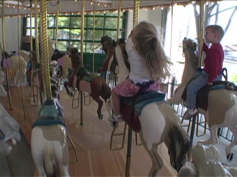 Children ride on a Merry Go Round Footage