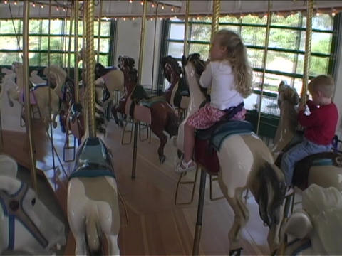 Children ride on a Merry Go Round Stock Video Footage