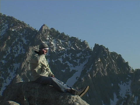 A man sits on a mountain peak and uses his cell phone Stock Video Footage