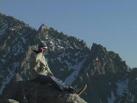 A man sits on a mountain peak and uses his cell phone Footage