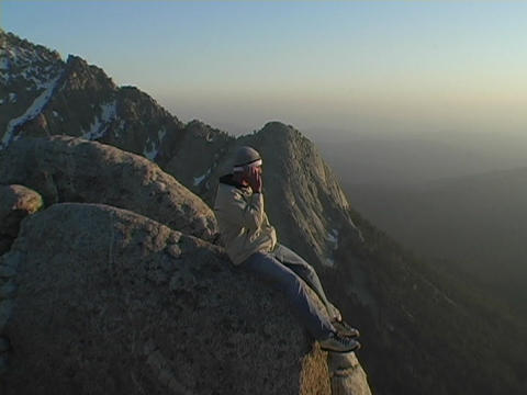 A man talks on a cell phone from a mountain peak Stock Video Footage
