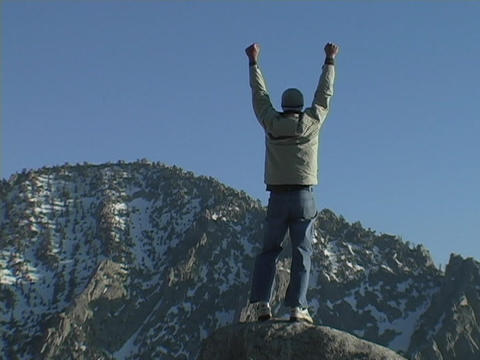 A hiker achieves his victory when he reaches the mountains summit Live Action