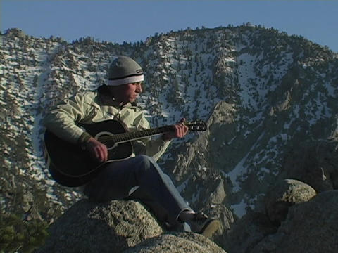 A man plays a guitar on a mountain Stock Video Footage