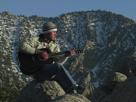 A man plays a guitar on a mountain Footage