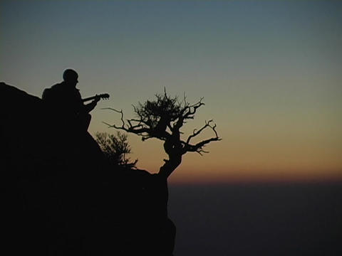 A man plays guitar on a mountain top Footage