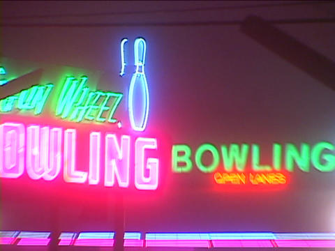 A neon sign is over the entrance to a bowling alley Footage