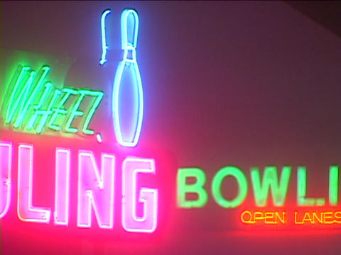 A neon sign is over the entrance to a bowling alley Stock Video Footage