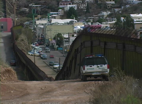 A police car watches the traffic on a busy street from a hill above Footage