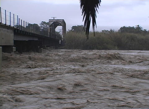 A raging river flows under a bridge in Santa Barbara, California Footage