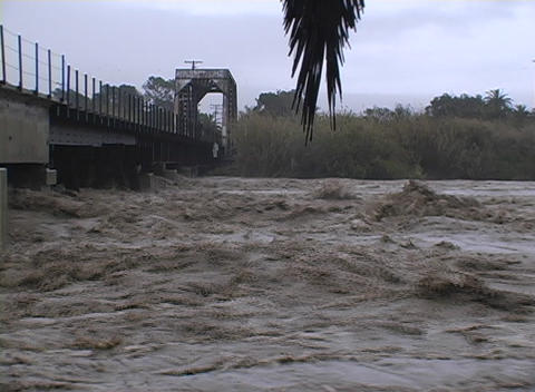 A raging river flows under a bridge in Santa Barbara,... Stock Video Footage
