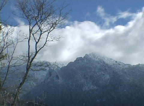 Clouds rapidly blow over majestic mountain peaks Stock Video Footage