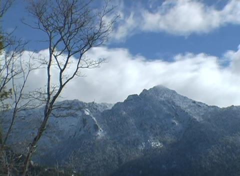 Clouds rapidly blow over majestic mountain peaks Footage