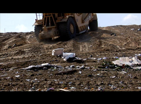 A large machinery moves through a garbage dump Stock Video Footage
