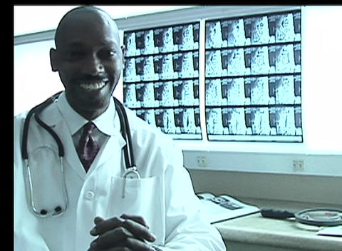 A doctor smiles at the camera after looking at x rays Stock Video Footage