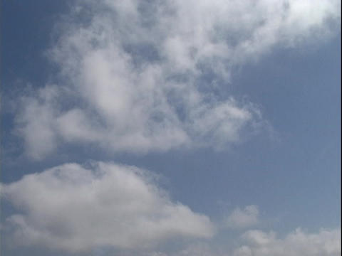 Clouds drift gently in a blue sky Stock Video Footage