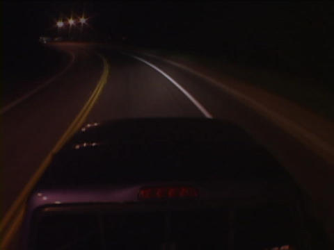 A car drives through a city at night Stock Video Footage
