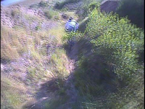 Mountain bikers cross rugged terrain Stock Video Footage