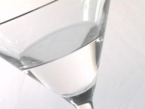 An olive on a toothpick falls into a martini glass Footage