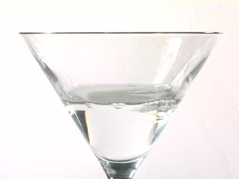 An olive drops into a martini glass Stock Video Footage