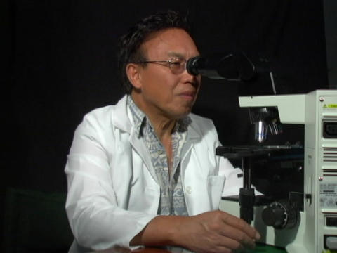 A man in a white coat looks up from a microscope Footage
