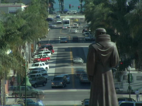 Traffic moves quickly on the streets adjacent to a statue of Junipero Serra Footage
