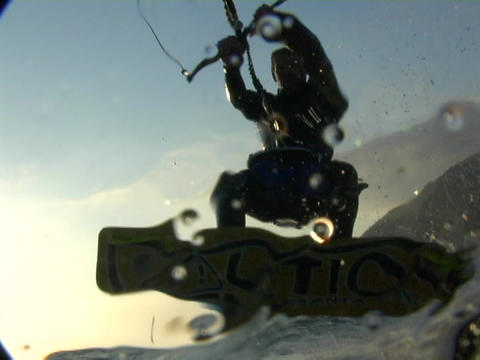 A kite-surfer sails over waves of the ocean Stock Video Footage