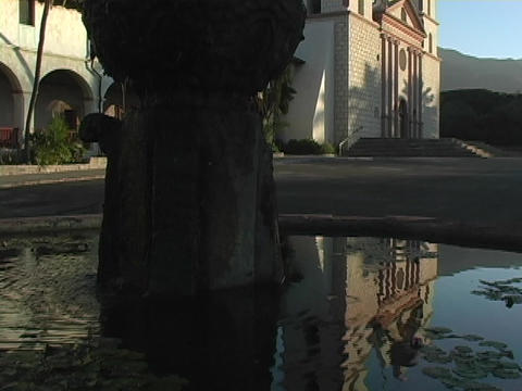 Still water in a fountain reflects a Catholic mission in Santa Barbara, California Footage