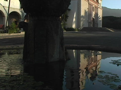 Still water in a fountain reflects a Catholic mission in Santa Barbara, California Live Action