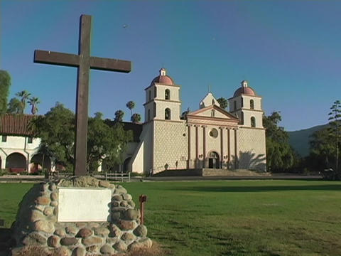 A plain cross embedded in stone occupies the lawn in front of a Catholic mission in Santa Barbara, C Footage