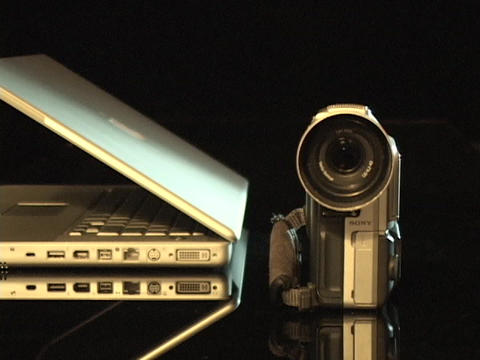 A digital camera sits beside a partially open laptop computer Footage