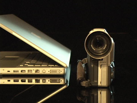 A digital camera sits beside a partially open laptop... Stock Video Footage