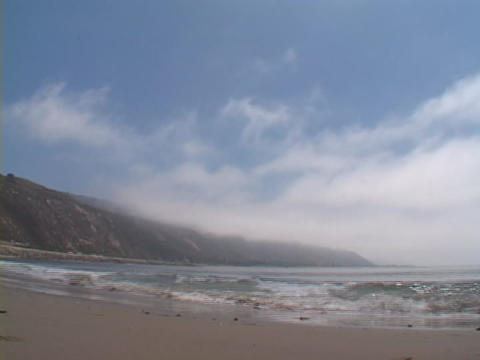 Waves rapidly roll onto a beach Footage