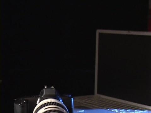 A digital camera lies next to a laptop computer Live Action