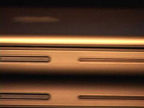 The edge of a laptop computer reflects silver light Footage